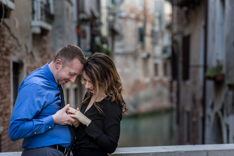 just-engaged couple looking at ring during engagement photo service