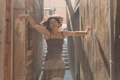 bride dances in a alley during a couple photo portrait in Venice