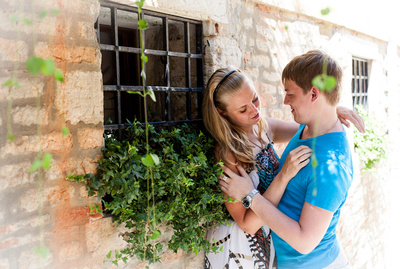 couple hugging next to a plant in an alley in Venice