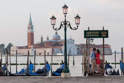 American couple kissing with lagoon in couple photo service in Venice