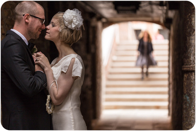 couple hugging under an arcade during wedding photo service in Venice
