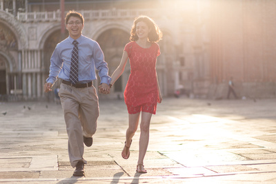 American couple running in San Marco Square during photo session in Venice