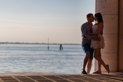 Russian couple kissing next to the sea at sunset during a honeymoon photo shooting