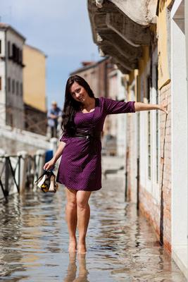 Beautiful Russian bride walks in high water during an informal photo walk in Venice