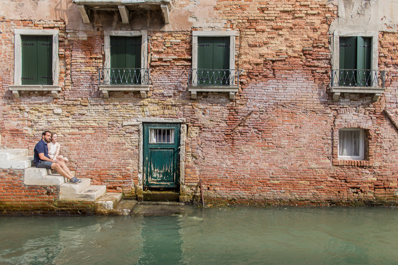 couple sitting during engagement photo walk in Venice