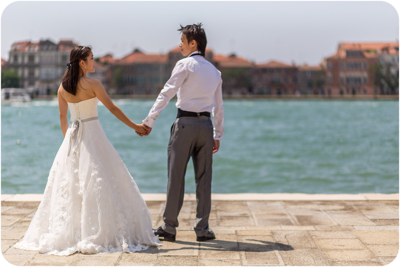 couple holding hands in front of lagoon during pre-wedding photo session in Venice