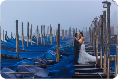 couple kiss among gondolas during couple portrait in Venice