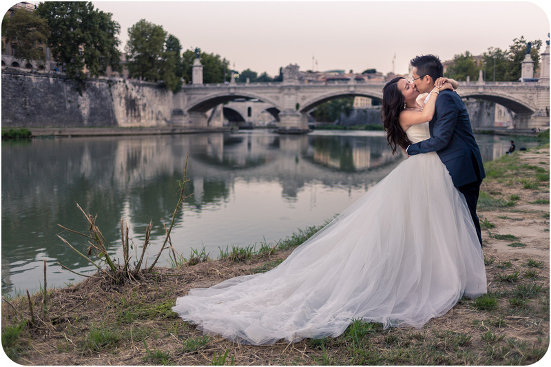 couple kissing next to Tiber River during honeymoon photography session in Rome