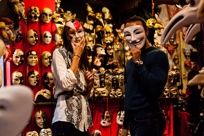 Russian couple playing with masks during a photo walk in Venice