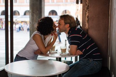 young couple posing in a café during a honeymoon photo shooting in Venice