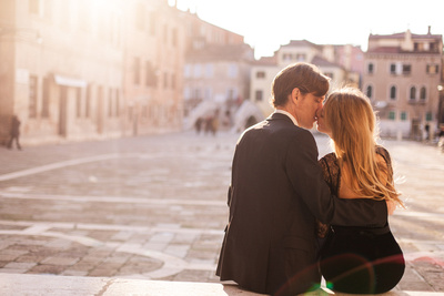 Canadian couple kissing in a small square during a honeymoon photo shooting in Venice