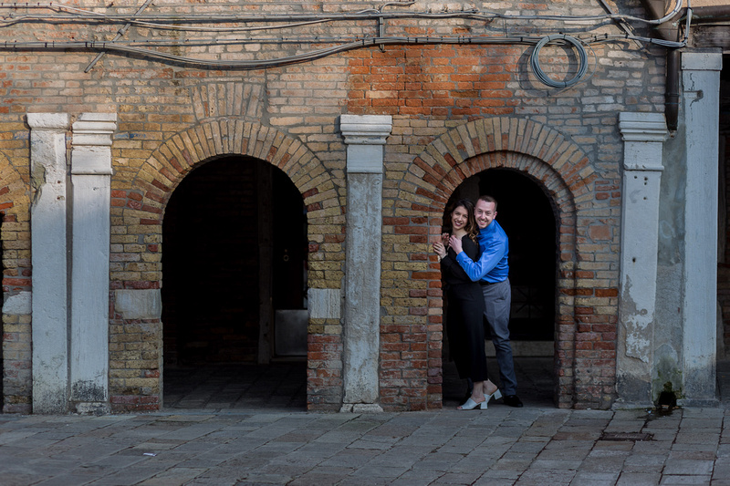 couple standing near an arch during engagement photo service in Venice