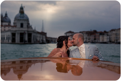 bride and groom kiss on watertaxi during wedding photo session in Venice