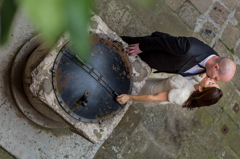 couple kiss next to well during romantic couple photo session in Venice