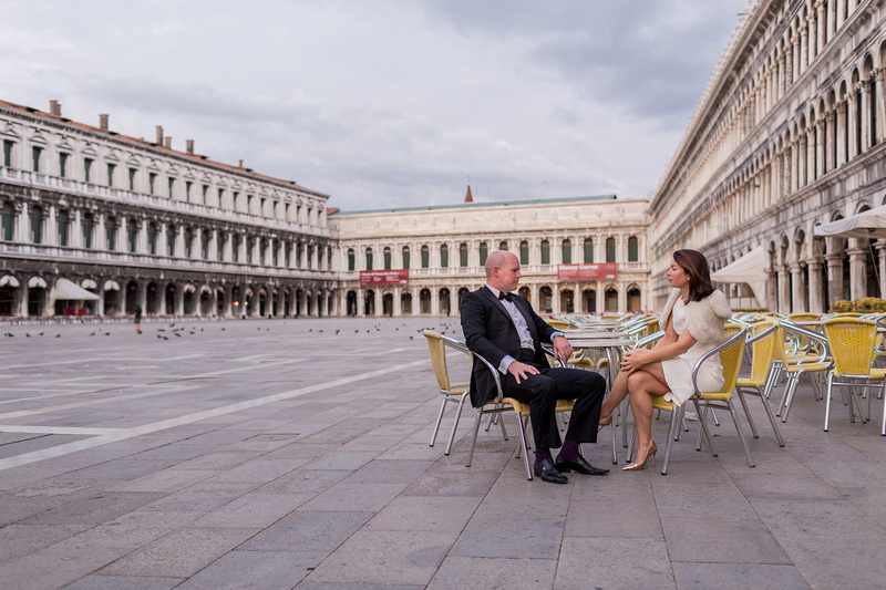 couple sitting in San Marco SQuare for couple photos in Venice at dawn