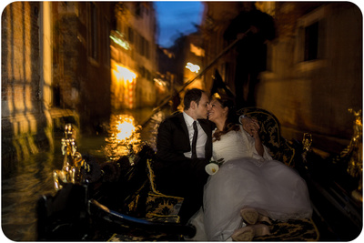 just-married couple kiss on gondola during wedding photo service in Venice