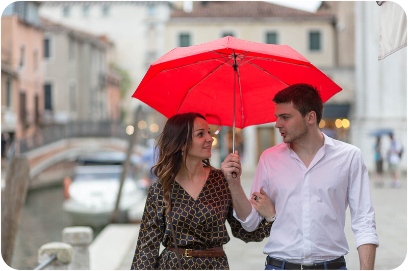 couple walking under umbrella during e-session in Venice