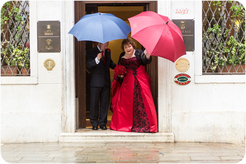 couple walking with umbrellas during wedding photo session in Venice