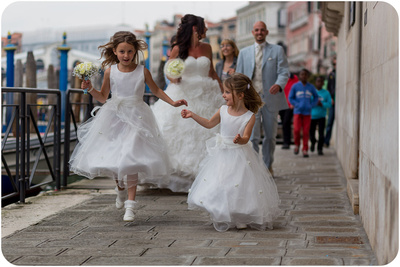 bride groom and kids walk during wedding photo session in Venice