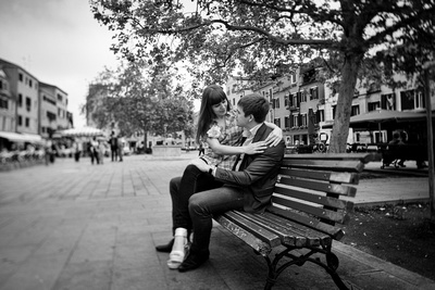 Russian couple sitting on a bench in a square during a honeymoon photo service in Venice.