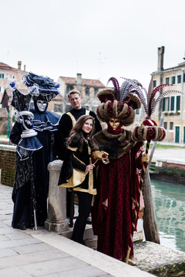 couple posing with actors wearing Venetian Carnival costumes during informal photo walk in Venice