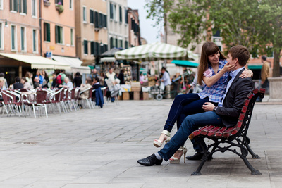 Russian couple sitting on a bench during honeymoon photo session in Venice