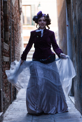 young lady in steampunk outfit runs in a alley during photo portraits in Venice