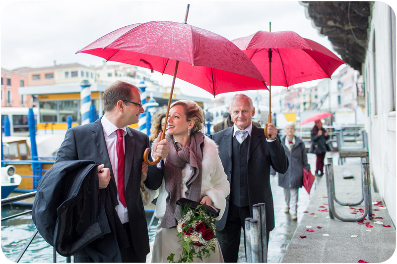 bride and groom walk under the rain during wedding reportage in Venice