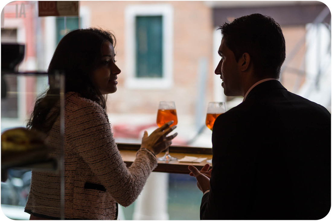 couple drinking in wine bar during wedding proposal photo session in venice